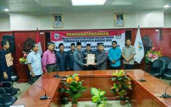Bupati Mura Perdie M Yoseph menyerahkan NPHD kepada Ketua KPU Mura sesudah penandatanganan di Aula Setda, Rabu (14/6/2017).