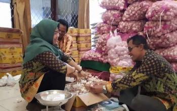 Kepala Bulog Divre Kotim, Joko Prasetyo Afrizal saat membantu petugas membersihkan bawang putih yang merupakan salah satu komoditi yang dijual pada operasi pasar murah, Kamis (15/6/2017)