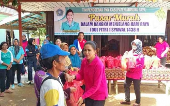 Ketua TP-PKK Kabupaten Mura saat menyerahkan paket makanan yang dijual mura pada kegiatan pasar murah di Kelurahan Muara Tuhup, Kecamatan Laung Tuhup, Jumat (16/6/2017).