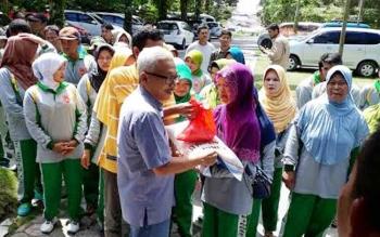Direktur HRD CBI Group Budi Setiawan menyerahkan paket zakat H Abdul Rasyid AS kepada petugas kebersihan pasar.