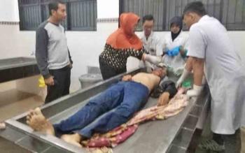 Tim medis sedang menangani korban di ruang jenazah RSUD dr Doris Sylvanus Palangka Raya. Kanit Laka Satlantas Polres Palangka Raya Aiptu Tri Marsono (kiri) mengecek langsung kondisi korban.