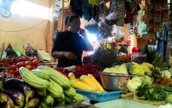 Seorang pedagang sayur di Pasar Kahayan, Palangka Raya menjual bawang merah, bawang putih dan cabai