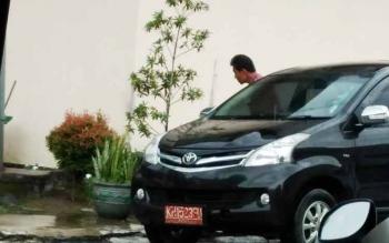 Seorang pegawai negeri sipil (PNS) keluar dari mobil dinas saat berada di halaman Pemda.