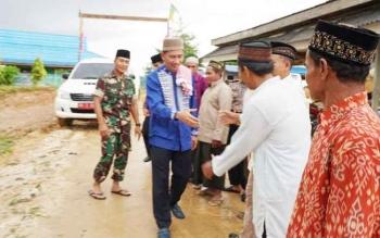 Bupati Barito Utara Nadalsyah menyalami warga saat melakukan safari Ramadan ke Masjid Baiturrahman, Desa Mampuak