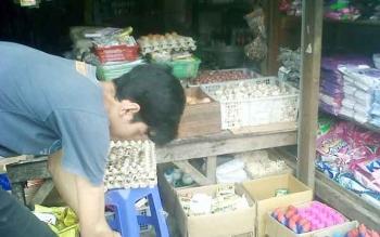 Salah seorang penjaga toko sembako di Pasar Kasongan tampak sibuk melayani pelanggannya, Senin (19/6/2017)