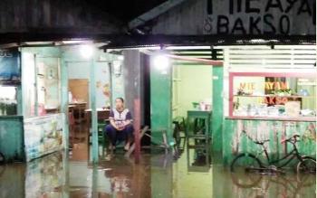Seorang pemilik warung di Jl HM Arsyad tidak dapat berjualan, karena tempatnya kebanjiran.