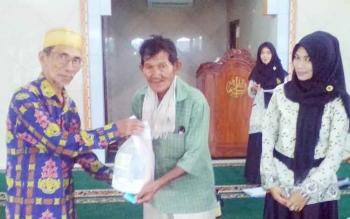 Ketua Demisioner PD Muhammadiyah Kuala Kapuas Kamarudin menyerahkan paket embako kepada seorang warga di Masjid Ar-Rahman, Jalan Barito, Kecamatan Selat, Selasa (20/6/2017).