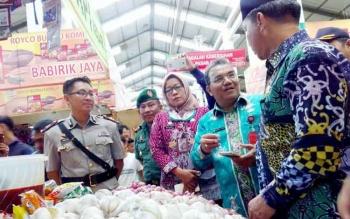 Wali Kota Palangka Raya Riban Satia saat mengecek harga bawang butih dan merah di Pasar Kahayan.