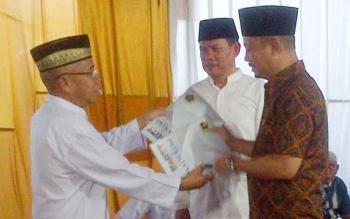 Ketua PWI Provinsi Kalteng Sutransyah (kiri) menyerahkan buku putih yang berisi nama anggota PWI kepada Bupati Barsel, Eddy Raya Samsuri pada safari ramadan dan buka puasa bersama di Buntok, Kamis (22/6/2017).