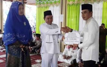 Bupati Kotim, Supian Hadi saat menyerahkan bantuan untuk masjid Raudhatul Jannah, kepada Camat Baamang Yusransyah, Kamis (22/6/2017)