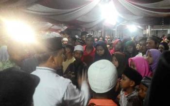 Wali Kota Palangka Raya Riban Satia (baju putih) berusaha mengatur barisan warga yang berdesak-desakan mengantre santuan, Kamis (22/6/2017).