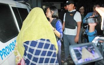 Polisi menggiring Fit, perempuan yang diduga selingkuhan terduga oknum Satpol PP Kapuas. Sedangkan sang oknum sendiri kabur