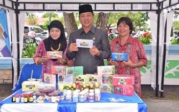 Wali Kota Palangka Raya, HM Riban Satia menujukkan produk UMKM dalam sebuah pameran