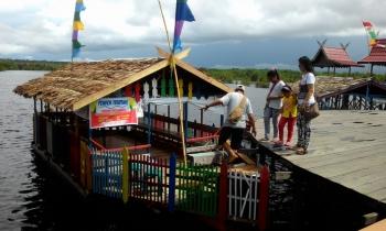 Satu keluarga pengunjung wisata Dermaga Kereng Bangkirai menaiki kapal wisata susur sungai, Sabtu (24/6/2017).