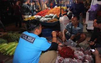 Kasat Reskrim Polres Palangka Raya AKP Ismantao Yuwono saat menginterogasi Parno, pedagang cabai di Pasar Besar, Sabtu (24/6/2017)
