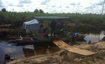 Sebuah feri tradisional menyusuri sungai kecil menuju Desa Talingke karena jalan yang ada masih terendam banjir, Senin (26/6/2017).