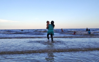 Sejumlah pengunjung sedang menikmati ombak di pantai sambil berenang.