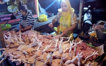 Seorang pedagang ayam di Pasar Rajawali, Palangka Raya sedang melayani pembeli