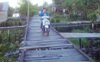 Pengendara motor melintas di Jembatan Panjang di Desa Murung Keramat, Kecamatan Selat, Kabupaten Kapuas, Jumat (30/6/2017).