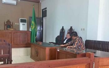 Rektor Universitas Palangka Raya 2005-2013, Henry Singarasa berdiskusi dengan penasehat hukum Dekie Kasenda sebelum dimulainya sidang dengan agenda pembacaan putusan.