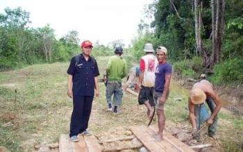 Petugas dari Dinas Pemberdayaan Masyarakat Desa Kabupaten Kapuas, Yeri Wartin (topi merah) meninjau proses pengerjaan jembatan yang mengunakan Dana Desa, beberapa waktu lalu.