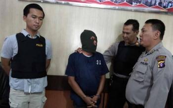 Polisi menginterogasi tersangka sabu bernama Gunawan (bertopeng).