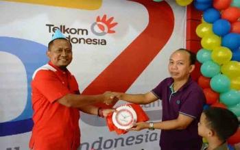 GM Telkom Witel Kalteng Slamet Riyanto Pardi (kiri) menyerahkan kejutan menarik kepada pelanggan yang beruntung di Plasa Telkom Palangka Raya, Kamis (6/7/2017)