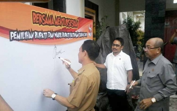 Plt Bupati Katingan Sakariyas disaksikan Ketua DPRD Ignatius Mantir L Nussa dan Ketua KPU Katingan membubuhkan tanda tangan komitmen mensukseskan Pilkada Katingan 2018.