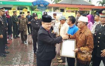 Ketua DPRD Barito Utara Set Enus Y Mebas menyerahkan piagam dari Polres kepada warga yang membantu tugas Polri saat perayaan HUT ke-71 Bhayangkara, Senin (10/7/2017).