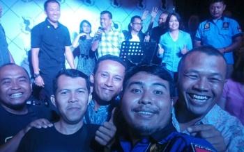 Sejumlah wartawan bersama aparat kepolisian berjoget sambil berfoto ketika Kapolres Palangka Raya AKBP Lili Warli didampingi jajaran bernyanyi pada acara silaturahim di Rollaas Coffee dan Tea, Jalan Antang, Palangka Raya.