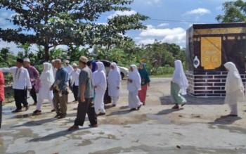 Tampak petugas kemenag Lamandau tengah membimbing calon jemaah haji melalui simulasi tawaf, Kamis (13/7/2017).