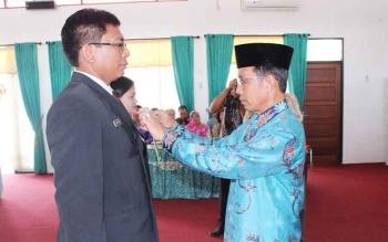Plt Sekda Kalteng Mugeni saat menyematkan tanda peserta Diklatpim III di Aula BPSDM Kalteng, Kota Palangka Raya, Kamis (13/7/2017).