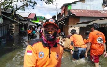 Petugas BPBD Kabupaten Mura tengah mengantar warga menyebarangi lokasi banjir di Jalan Temanggung Silam, Kota Puruk Cahu, Senin (17/7/2017).