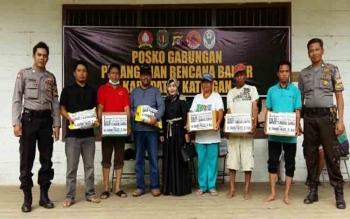 Fahmi Fauzi (topi hitam) dan istrinya foto bersama warga penerima bantuan di posko gabungan di Tumbang Samba, Selasa (18/7/2017)