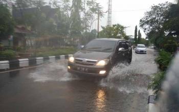 Sebuah mobil melintas di Jalan A Yani, Kota Sampit, yang tergenang, beberapa waktu lalu.
