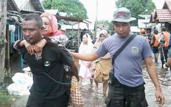 Petugas menggendong lansia warga Kampung Banjar yang ingin beeobat di posko banjim Kamis (20/7/2017)