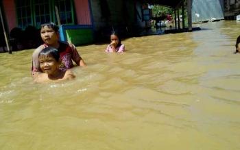 Anak-anak bermain-main di tengah banjir di Desa Pahawan, Kecamatan Banama Tingang, Kabupaten Pulang Pisau, Kamis (20/7/2017).