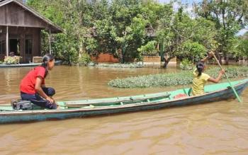 Dua remaja putri mengayuh jukung di tengah kondisi banjir di Desa Pahawan