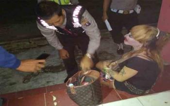 Barang bawaan milik seorang waria di Sanaman Mantikai diperiksa polisi