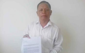 Radiansyah menunjukkan laporannya terhadap Ketua Koperasi Pamalian Bauntung, M.