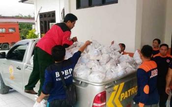 Petugas dari BPBD Kabupaten Gunung Mas menyalurkan bantuan untuk korban banjir di Kelurahan Tampang Tumbang Anjir, Jumat (21/7/2017).