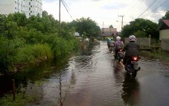 Sejumlah pengendara sepeda motor harus menyusuri jalan yang terendam banjir arah Kampung Banjar Kelurahan Kasongan Lama, Jumat (21/7/2017)