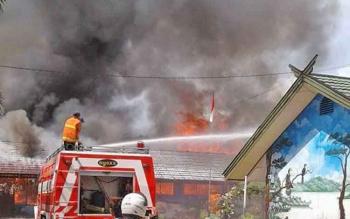 Petugas pemadam sedang menyemprotkan air ke bangunan SDN 4 Menteng yang terbakar, Jumat (21/7/2017)
