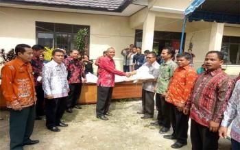 Asisten III Setda Gunung Mas Yohanes Tuah secara simbolis menyerahkan bantuan dari Pemkab Gumas untuk korban banjir yang diwakili lurah dan kepala desa, Jumat (21/7/2017).
