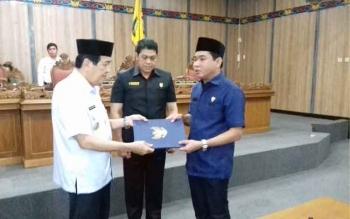 Ketua DPRD Kabupaten Kotawaringin Timur Jhon Krisli saat menyerahkan raperda yang sudah dibahas beberapa waktu lalu kepada Wakil Bupati Taufiq Mukri.