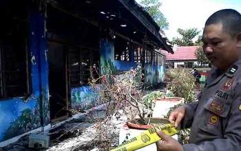 Petugas memasang garis polisi di SDN 4 Menteng yang terbakar, Jumat (21/7/2017) siang.