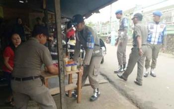 Anggota Satpol PP Murung Raya saat menertibkan lapak pedagang yang masuk badan jalan di Jalan Temanggung Silam, Kota Puruk Cahu, Senin (24/7/2017).