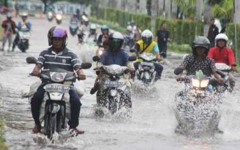 Pengendara menembus banjir yang terjadi di Jalan Yos Sudarso, Kota Palangka Rara beberapa waktu lalu