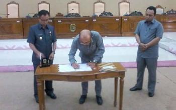 Ketua DPRD Ignatius Mantir L Nussa menandatangani dokumen 13 buah raperdayanv disetujui menjadi perda disaksikan Plt Bupati Sakariyas dan Waket II Alfujiansyah, Senin (24/7/2017).