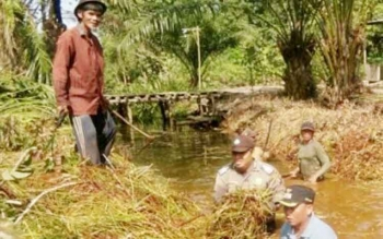 Bhabinkamtibmas Polsek Kapuas Murung Bripka Hendra Sedang Melakukkan Gotong Royong.